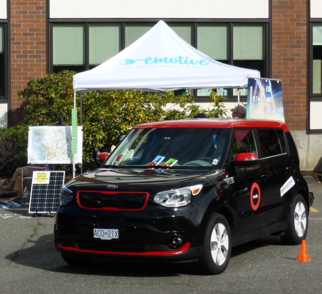 Modo's Kia Soul EV in front of the emotive tent