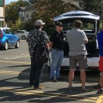 Owners discussing EVs with interested visitors